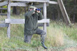 Jäger mit Fernglas vor Hochsitz