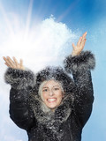 Pretty young woman with pelt cap is playing with snow poster