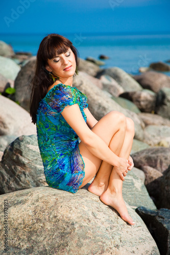 beautiful brunette girl sitting on beach stones