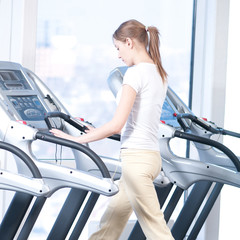 Young woman at the gym exercising. Running