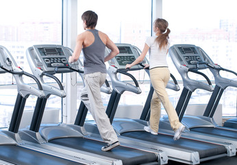 Young woman and man at the gym exercising. Running