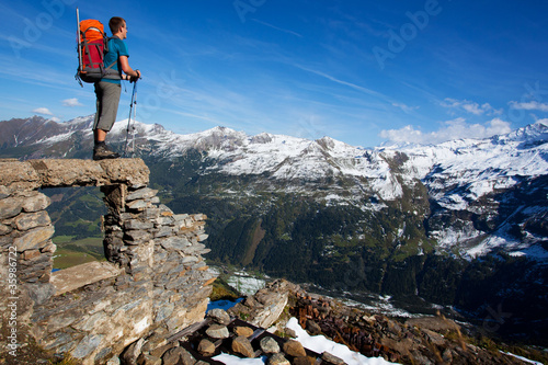 Young man with backpack enjoying mountain view