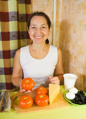 woman with ingredients for stuffed tomato salad