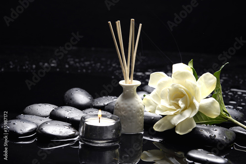 candle with gardenia flower and zen stones