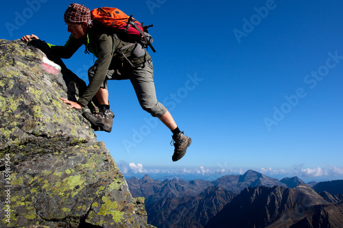 Young man climbing the mountain ridge