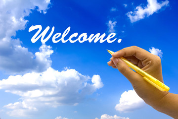 Hand writing welcome on blue sky.