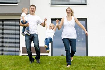 junge Familie vor neuem Haus