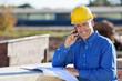 handwerker telefoniert auf der baustelle