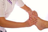 Therapeutin massiert Füße eines Mannes in Reflexzonen