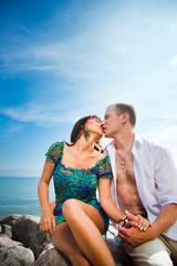 Kiss of loving couple near of blue sea