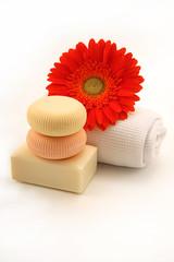 saponette con fiore rosso e asciugamano fondo bianco