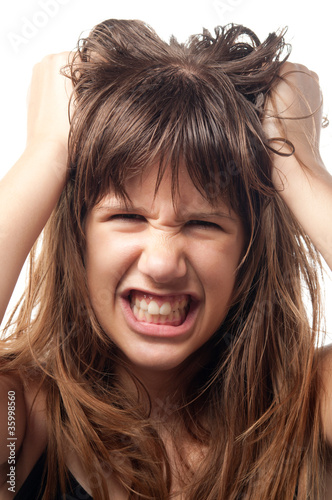 Angry and frustrated teenage girl grinding with teeth.