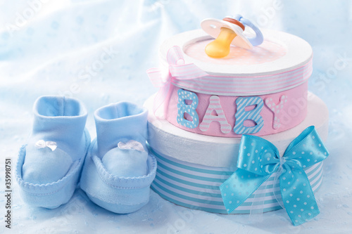 Leinwandbild Motiv Little baby booties and gift boxes