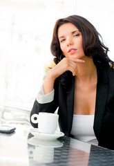 Portrait of pretty young business woman sitting relaxed at outdo