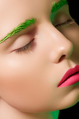 Girl with creative makeup, green eyebrows, pink lips