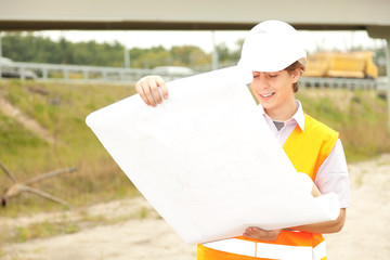 male engineer looking at blueprints in construction site