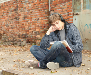 sitting male student learning near the brick wall