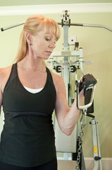 Attractive blond woman using exercise equipment