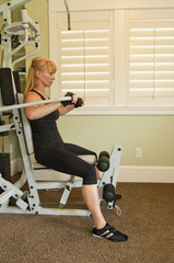 Attractive blond woman using exercise machine
