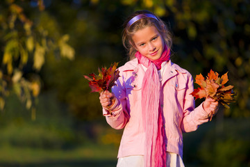 Young girl with leaves in autumn park