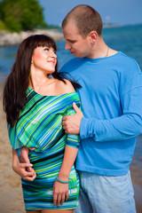Loving couple embracing on coast of blue sea