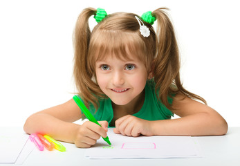 Cute little girl draws with markers