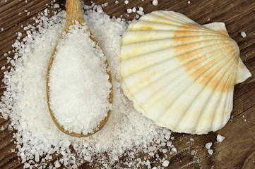 Coarse sea salt on a wooden table with spoon and scallop shell