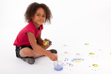 Little African Asian girl painting on the floor
