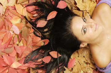 smiling young woman lying on red-brown leaves