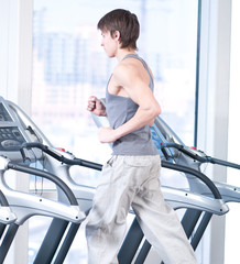 Young man at the gym exercising. Running