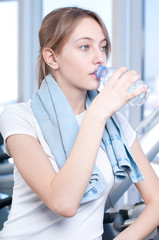 Woman at the gym exercising. Run on on a machine and drink water