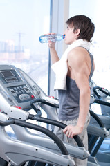 man at the gym drinking water
