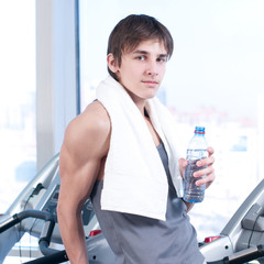 man at the gym exercising. Run on on a machine and drink water