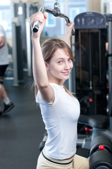 Powerful casual woman lifting weights in gym