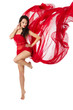Woman dancing in red flying waving dress  on a wind flow. Over w