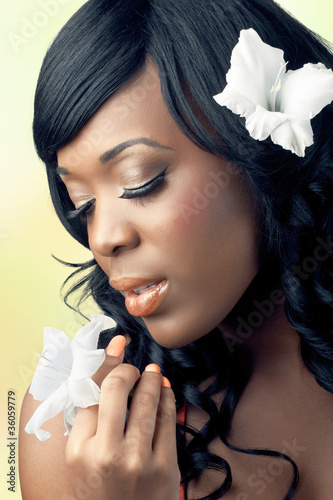 Beautiful young woman holding a white flower near her face