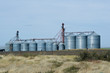 Steel grain storage silos with harvested field