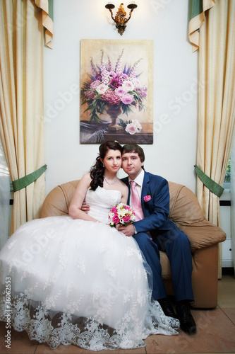 Happy bride and groom in sofa