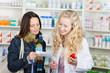 apothekerin und kunden schauen auf rezept