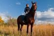 Pretty girl riding horse front of reed