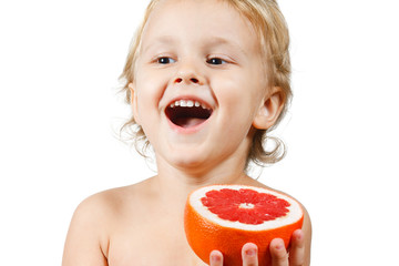 Little boy with a pink grapefruit on a white background