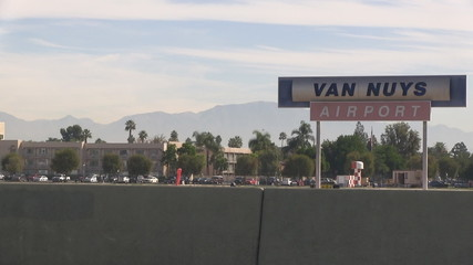 Establishing shot of Van Nuys Airport; slow zoom out on sign.