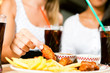Zwei Frauen essen Chicken wings und trinken Cola