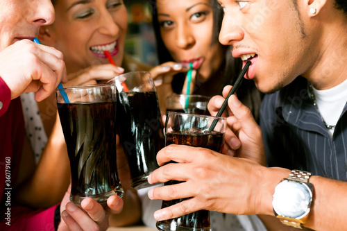 Friends drinking soda in a bar - 36079168