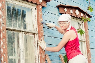 Young woman making cosmetic alterations of house