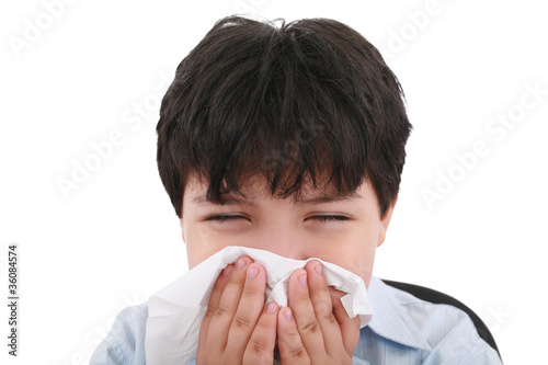 sick boy blowing his nose, white background
