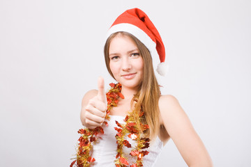 Girl in Santa hat showing thumbs up.