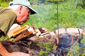 Senior man making bonfire