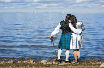 Woman and man in scottish costume looking at the sea.