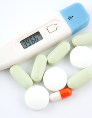 Some medical  pills and digital thermometer